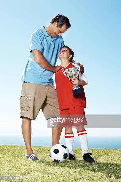 Happy father with his son holding a winners trophy