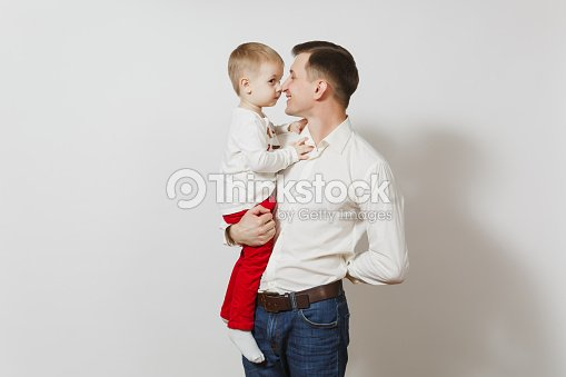 20314876 Happy Father's Day. Handsome joyful smiling young man holding and hugging  little cute child boy isolated on white background. Father and his little  kid son.