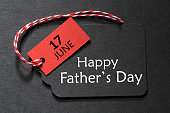 Happy Father's Day text on a black tag with red and white twine