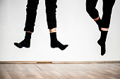 Close up image of two pairs of legs, wearing black pants and black socks beyond the parquet. Both persons are in jump and one has flat feet and the other has crossed with points. White wall in the bac