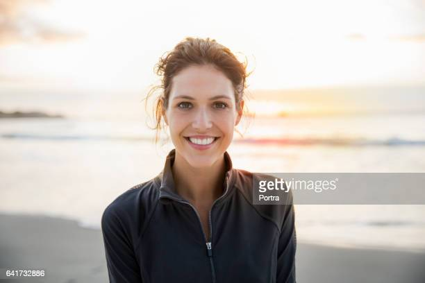Happy female athlete at beach during sunset
