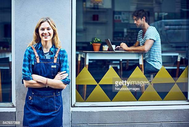 Happy female barista with arms crossed outside cafe