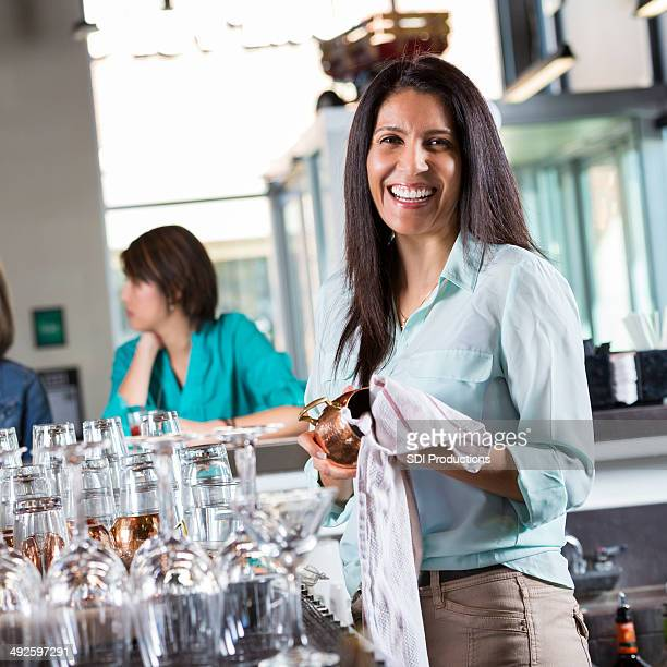Happy female bartender cleaning glass ware at bar