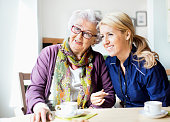 Happy female caretaker and senior woman looking away while sitting at table in nursing home