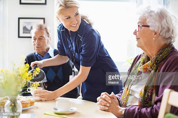 Happy female caretaker serving coffee to senior people at nursing home