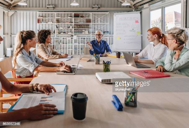 Happy female CEO talking to her female team on a business presentation in the office.