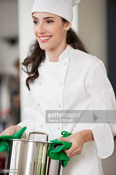 Happy female chef holding a saucepan