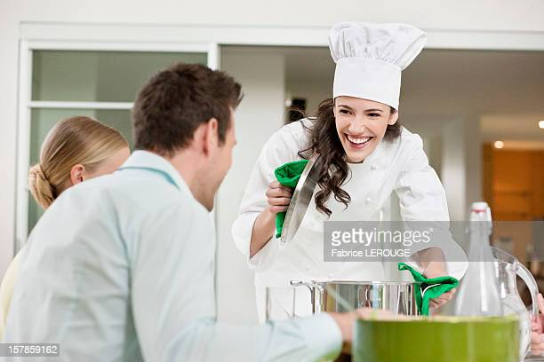 Happy female chef serving food