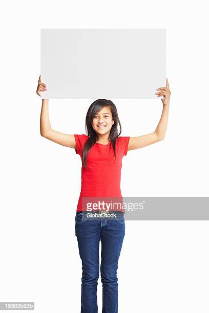 Happy female child holding up a blank billboard with copyspace