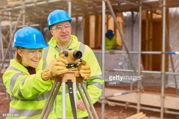 happy female construction trainee with tutor