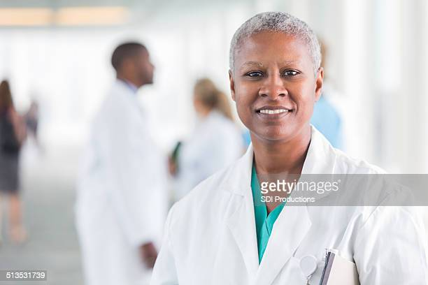 Happy female doctor smiling while walking in hospital hallway