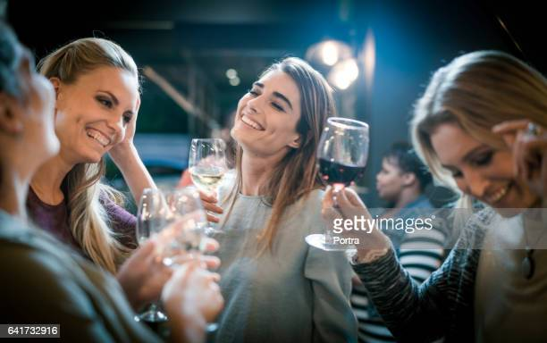 Happy female friends dancing while having drinks in bar