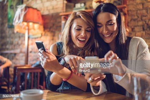 Heureux femmes amis, lire un SMS sur son téléphone cellulaire.