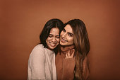 Two young woman standing together in studio and smiling. Happy female friends smiling together against brown background.