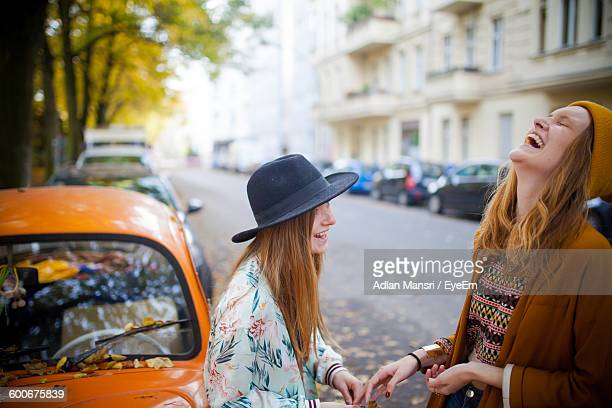 Happy Female Friends Standing By Cars On Road