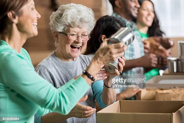 Happy female friends volunteer at charity food bank