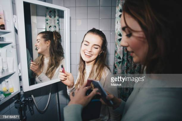 Happy female friends with mobile phone and lip gloss at dorm bathroom