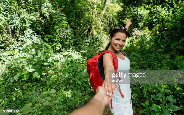 Happy female hiker holding the hand of her partner