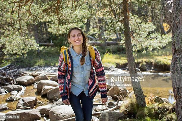 Happy female hiker walking in forest