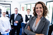 Portrait of happy female manager standing with arms crossed in restaurant