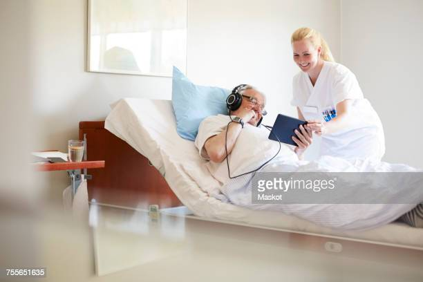 Happy female nurse assisting senior man in using digital tablet on hospital bed