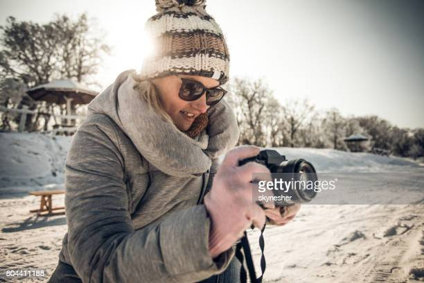 Happy female photographer taking a photo in winter day.