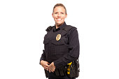 Portrait of happy female police officer standing against white background