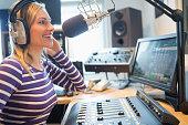 Close-up of happy female radio host broadcasting through microphone in studio