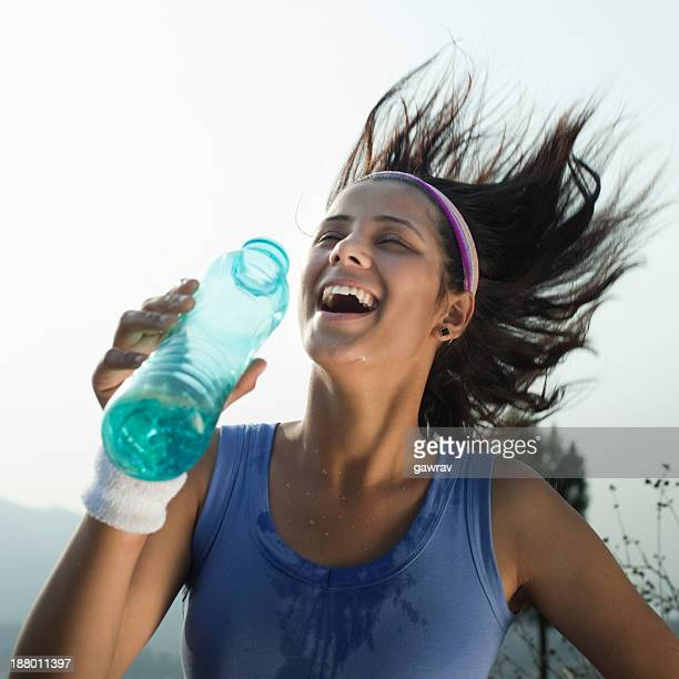 Happy female runner splashing water on her body.