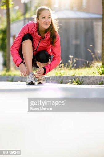 happy female runner tying shoe lace