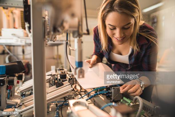Happy female student examining manufacturing equipment in laboratory.