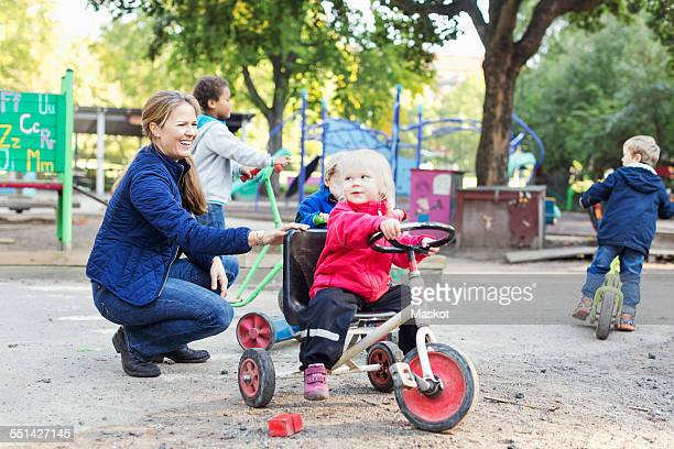 Happy female teacher assisting girl to ride tricycle on playground