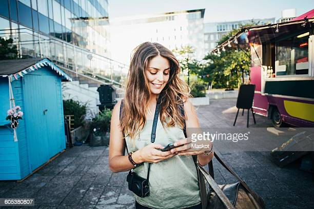 Happy female tourist using smart phone in city