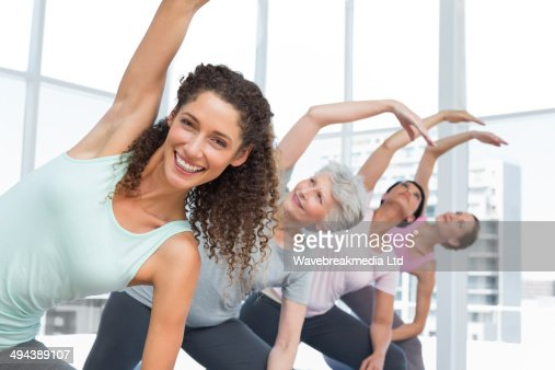 Class stretching hands at yoga class : Foto stock