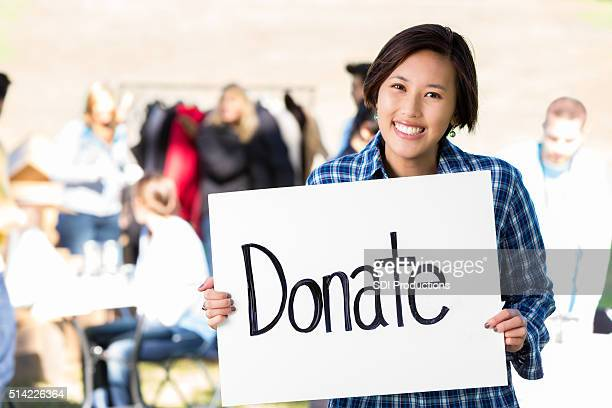Happy female volunteer at clothing drive