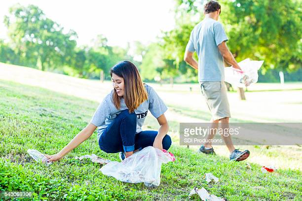 Happy female volunteer picks up trash in park