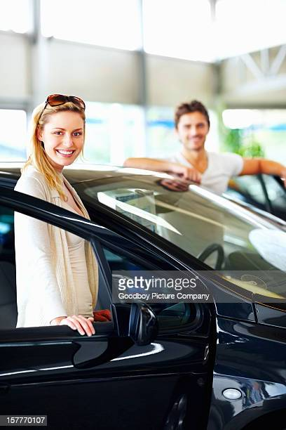 Happy female with boyfriend standing by new car at showroom