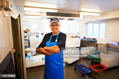 Happy fishmonger in his workplace