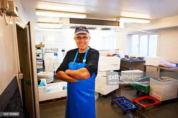 Heureux Le fishmonger'dans son lieu de travail