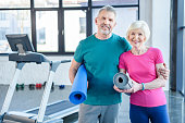 Happy fitness couple holding yoga mats and smiling at camera in gym