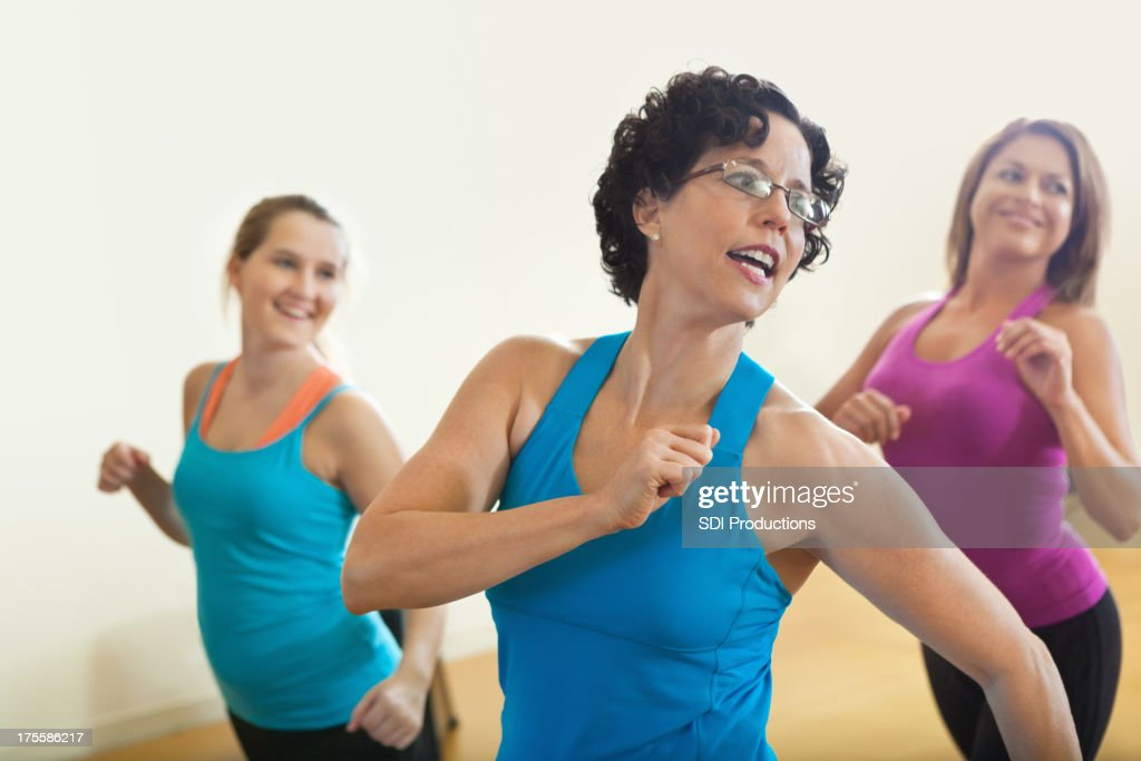 Happy fitness instructor teach in class to smiling students : Stock Photo