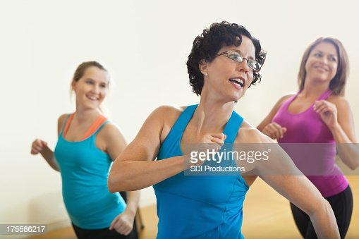 Happy fitness instructor teach in class to smiling students
