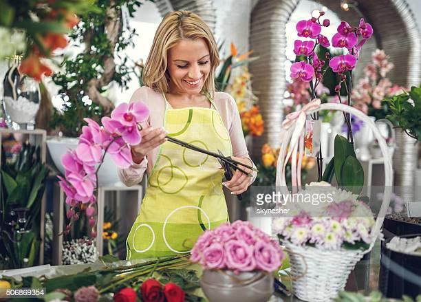 Happy florist working in flower shop.