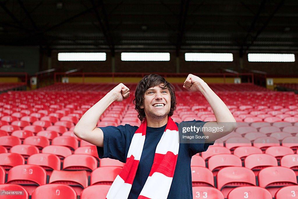 Happy football fan in empty stadium : Stock Photo
