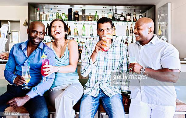 Happy foursome socializing in hotel bar
