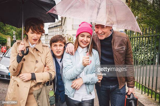 Happy french family out in the rain