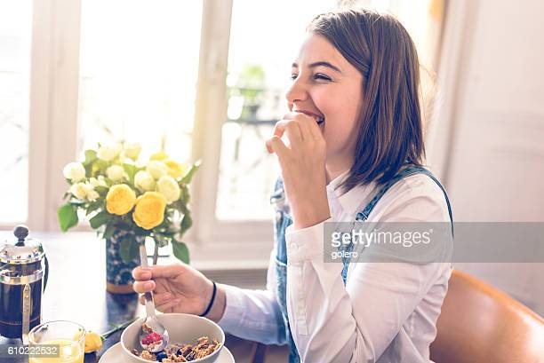 happy french teenage girl with cereals at breakfast table