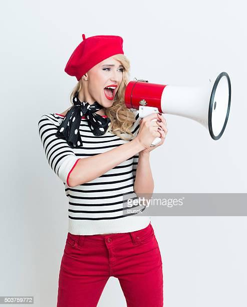 Glücklich-Frau mit roten Baskenmütze schreien auf Megafon