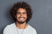 Portrait of a happy cheerful young man looking at camera. Handsome young man with beard and curly hair standing against grey background. Close up face of multi ethnic young man isolated against grey w