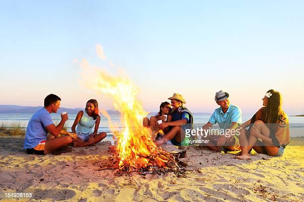 Heureux amis passent, assis à côté d'un feu de camp.